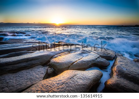 the breaking dawn over a rocky shore and lively sea - stock photo