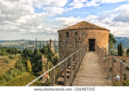 The brickwalls of the medieval Fortress of Venetians in Brisighella. Cultivated fields and the Clock Tower in the background - stock photo