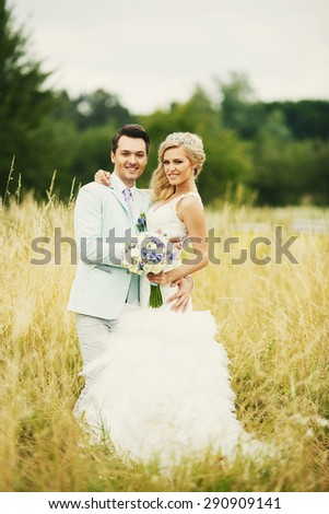 The bride and groom are standing in an open field in yellow