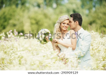 The bride and groom are standing in an open field in yellow where many flowers