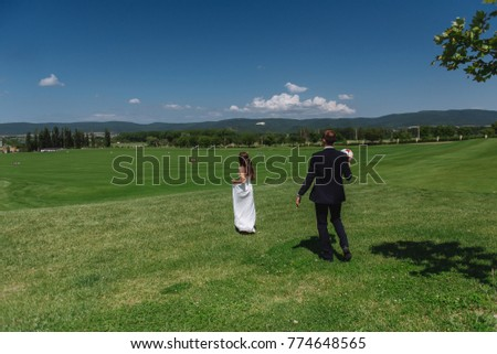 The bride and groom are walking along the beautiful grass in the park. Landscape