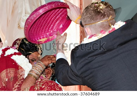 The bride and groom dump rice on each other during a traditional Hindu wedding ceremony - stock photo