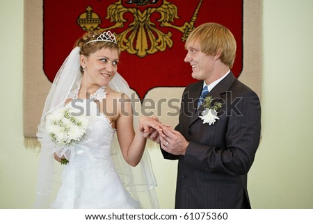The bride and groom exchange rings on the background of the national coat of arms - stock photo