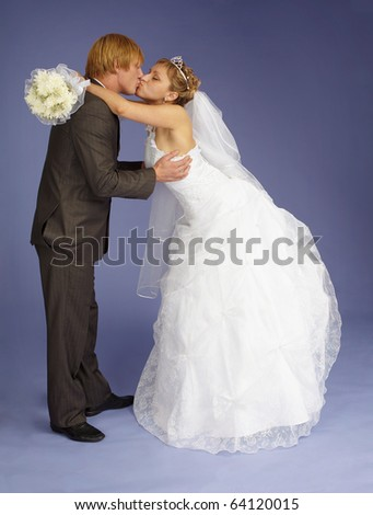 The bride and groom funny kiss on purple background - stock photo