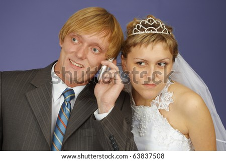 The bride and groom get a phone call - stock photo