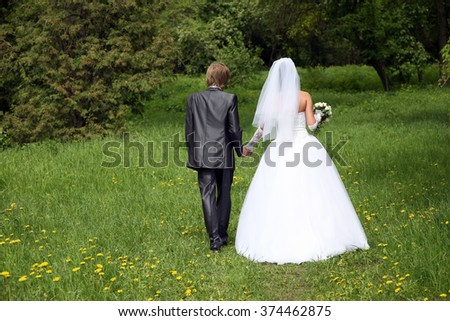 the bride and groom goes along the grass