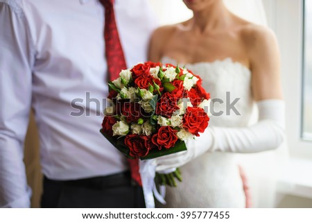 The bride and groom holding a bouquet of white and red roses. The groom in a shirt and red tie. The bride in a dress and white gloves. Focus on flowers. - stock photo