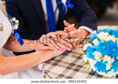 The bride and groom holding hands on a wooden desk, restaurant.