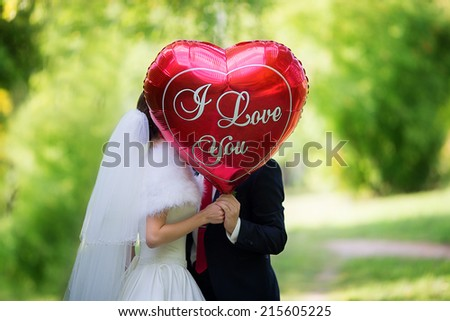 "The bride and groom in the Park with the red balloon with the words ""I love you"" - stock photo"
