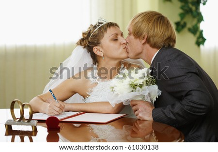 The bride and groom kiss during the ceremony of marriage - stock photo