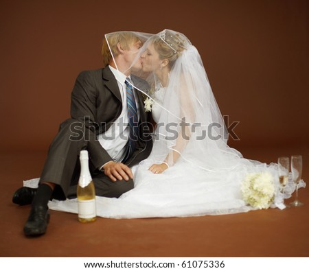 The bride and groom kissing and drinking champagne wine - stock photo
