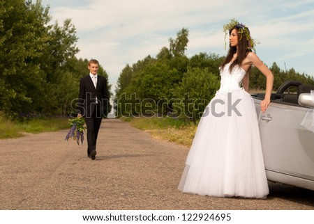 The bride and groom on the background of nature in a  cabriolet - stock photo