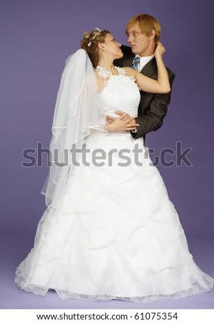 The bride and groom pose on studio - stock photo