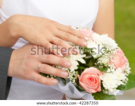 The bride and groom's hands together on the wedding bouquet - stock photo