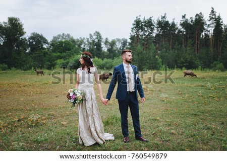 The bride and groom stand holding hands on the background of nature. Summer wedding walk on a green glade.