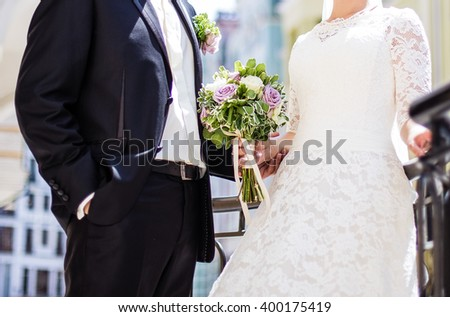 The bride and groom standing together on the street