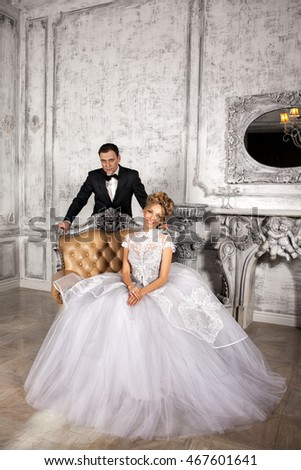 the bride and groom. the bride in an elegant dress sits a luxurious chair, the groom stands behind her. Studio. gray room