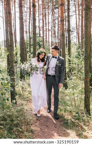 the bride and groom walk in the woods - stock photo