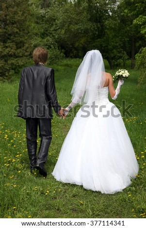 the bride and groom walking on the grass with flowers