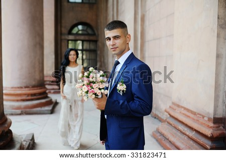 the bride and groom  with a wedding bouquet on the background of an old building with columns