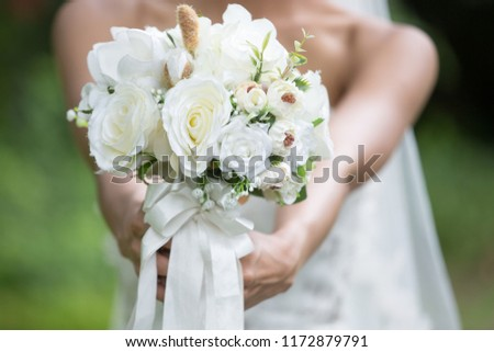 The bride carries a bouquet of flowers received from the groom happily.