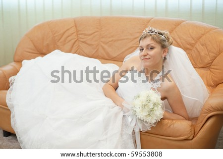 The bride comfortably lies on the big leather sofa - stock photo