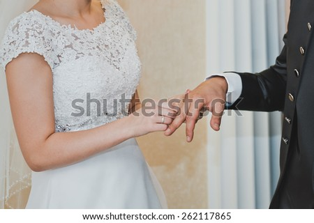 The bride dresses a ring on a finger of the groom. - stock photo