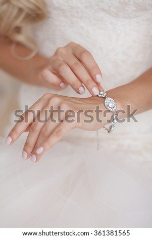 the bride dresses the bracelet on a hand - stock photo