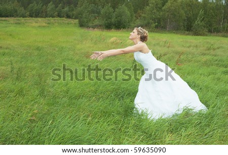 The bride hastens towards to the groom on a green meadow - stock photo