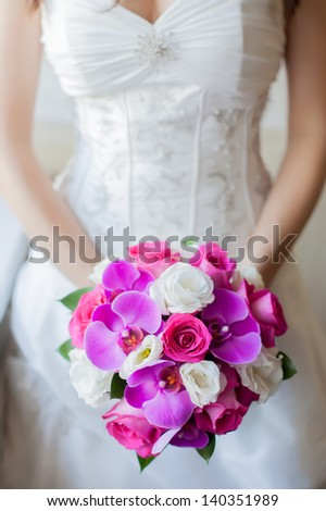 the bride holds a beautiful bouquet from pink and white flowers