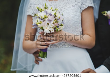 The bride holds a bunch of flowers.