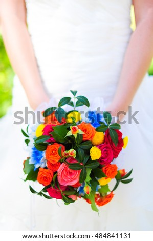 the bride holds a colorful bouquet. Wedding