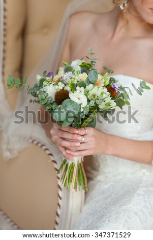 the bride holds a gentle bouquet in hand