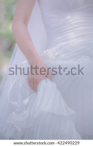 The bride holds a wedding dress in the assembly. - stock photo