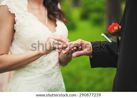 The bride holds the hand of her handsome groom and puts his wedding ring