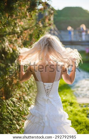 The bride in a dress in a clearing near the ancient castle before the wedding ceremony - stock photo