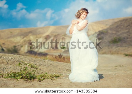 The bride in a wedding dress in the middle of the desert