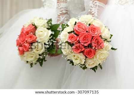 The bride in a white dress at a wedding ceremony with a bouquet of roses. - stock photo