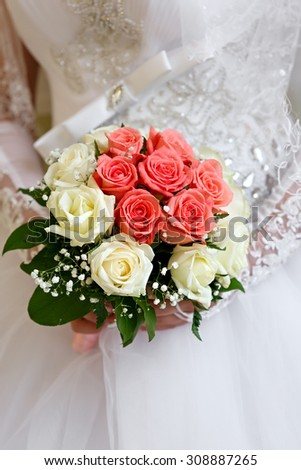 The bride in a white dress at a wedding ceremony with a bouquet of roses.