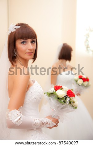 The bride in a white dress with a wedding bouquet and its reflection in the mirror