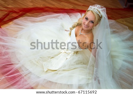 The bride in white dress sitting on the floor. - stock photo