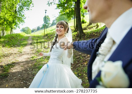 The bride is leading groom on a road - stock photo