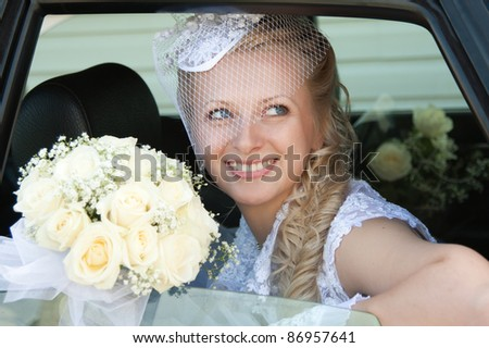 The bride is looking out the car. Wedding day - stock photo