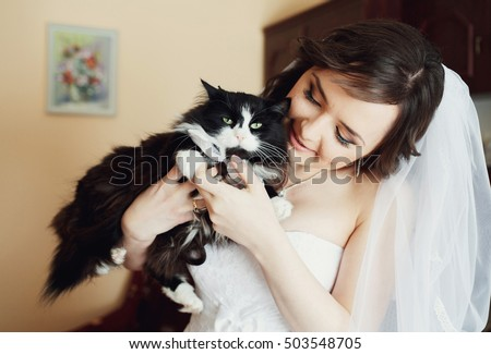 The bride is playing with the cat