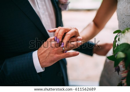 The bride puts on the engagement ring to the groom