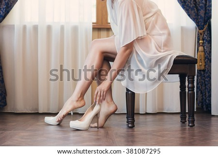 the bride puts on white shoes on feet - stock photo