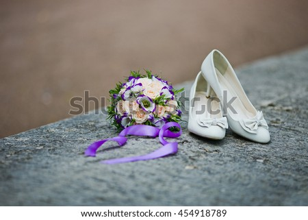 the bride's bouquet on stone background with white shoes. wedding concepts - stock photo