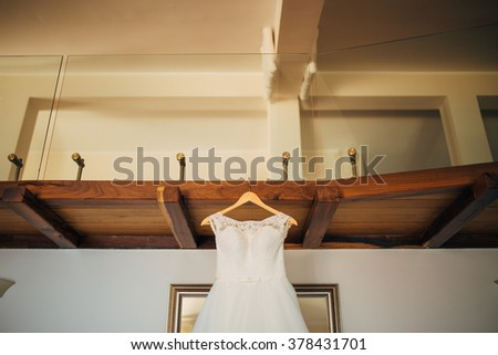 The bride's dress on a hanger in the room