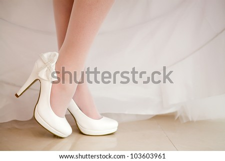 The bride shows white wedding shoes - stock photo