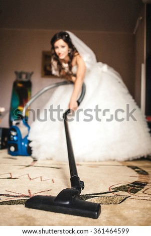 the bride vacuums a carpet in the room - stock photo